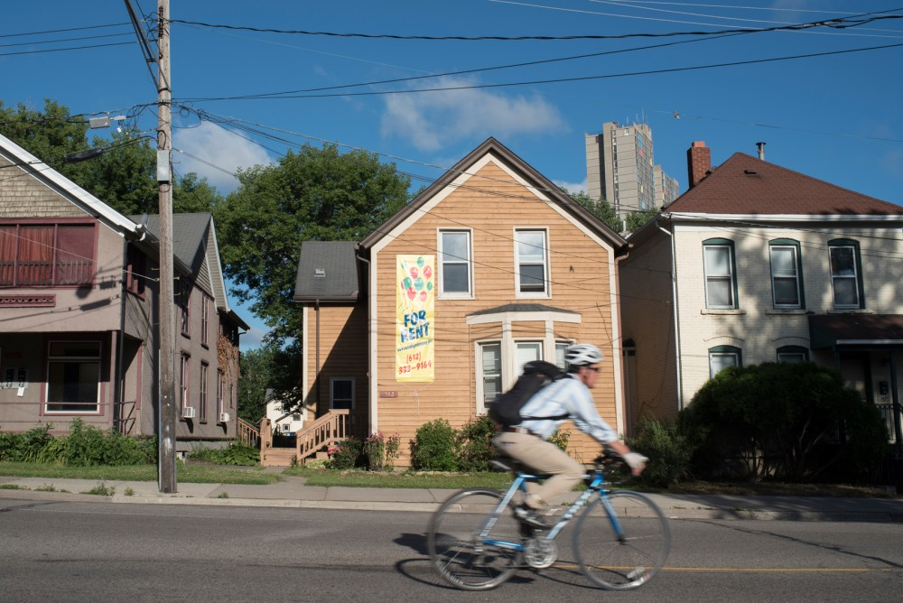 A biker rides down 20th Ave S in the Cedar Riverside neighborhood on the morning of 28 June. Minneapolis city council members Abdi Warsame and Elizabeth Glidden are working on a bill which would prevent landlords from denying prospective renters based solely on their Section 8 status.