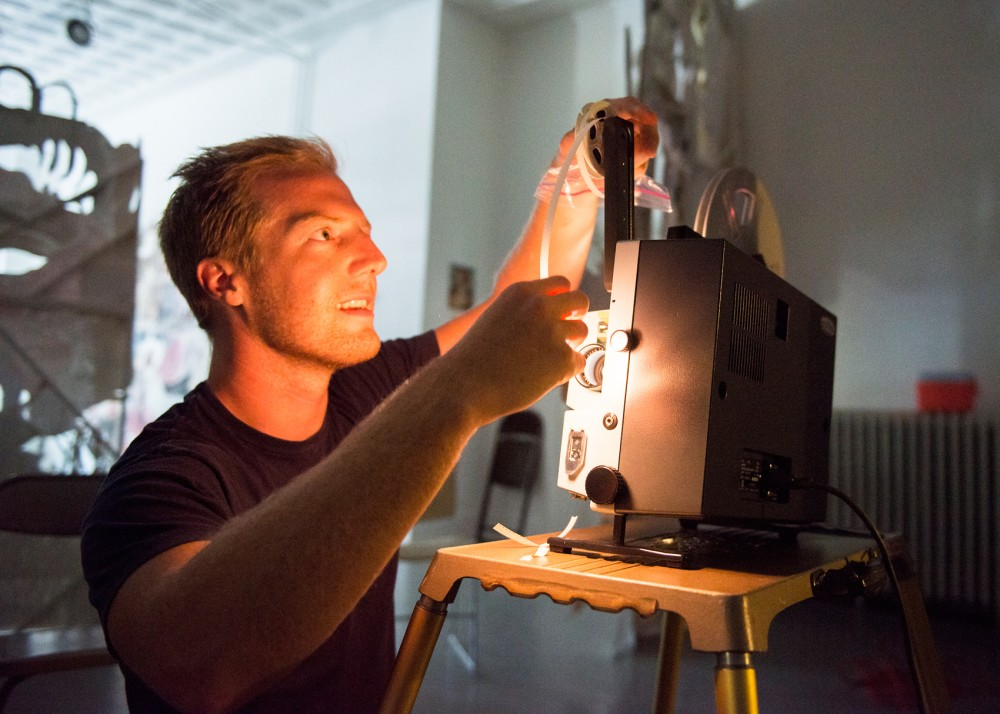 University graduate Tyler Lauer feeds his film reel through a projector at the White Page Gallery for a prescreening on Monday. Lauer is a part of the upcoming Movies at WAM, a showcase of home movies brought by attendees, and work from contemporary film artists, all projected across a spectrum of classic film types.