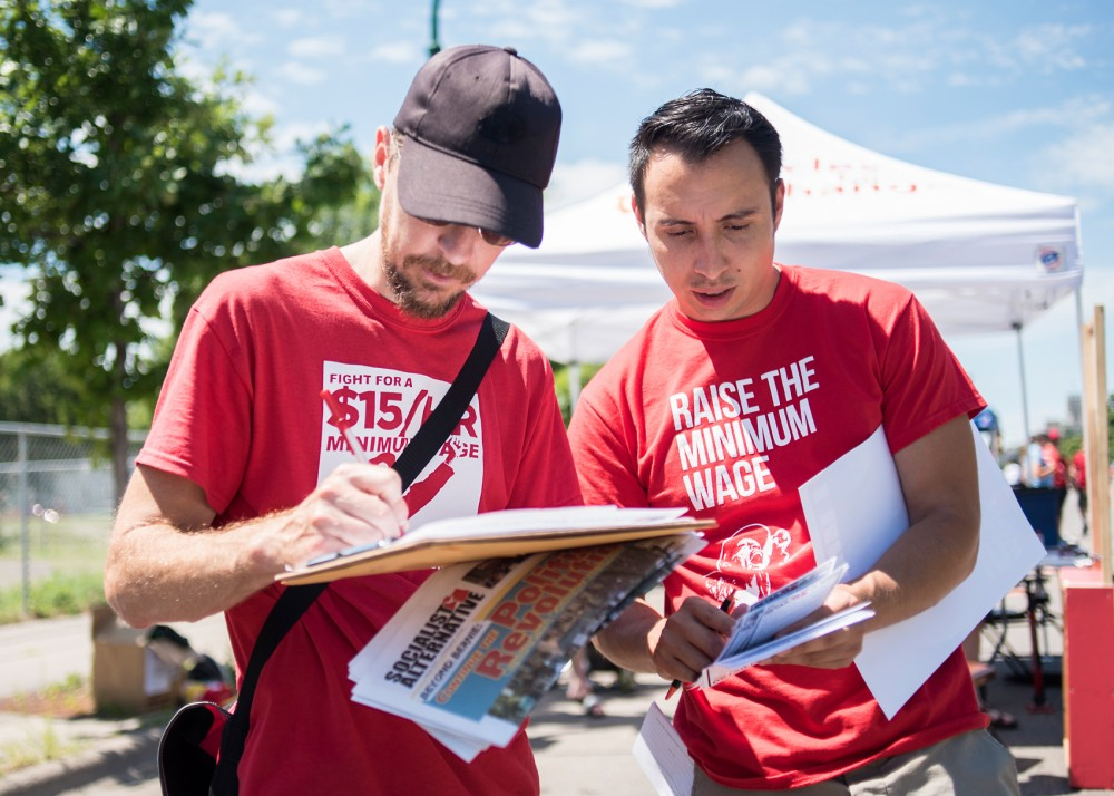 Luke Gitar and Nestor Garcia of Minneapolis talk during their work to raise awareness for the 15 Now campaign while at Open Streets Minneapolis: East Lake on Sunday. Campaigning to increase minimum wage to $15 an hour, 15 Now obtained nearly 20,000 signatures, more than enough to make it onto the November 2016 ballet.