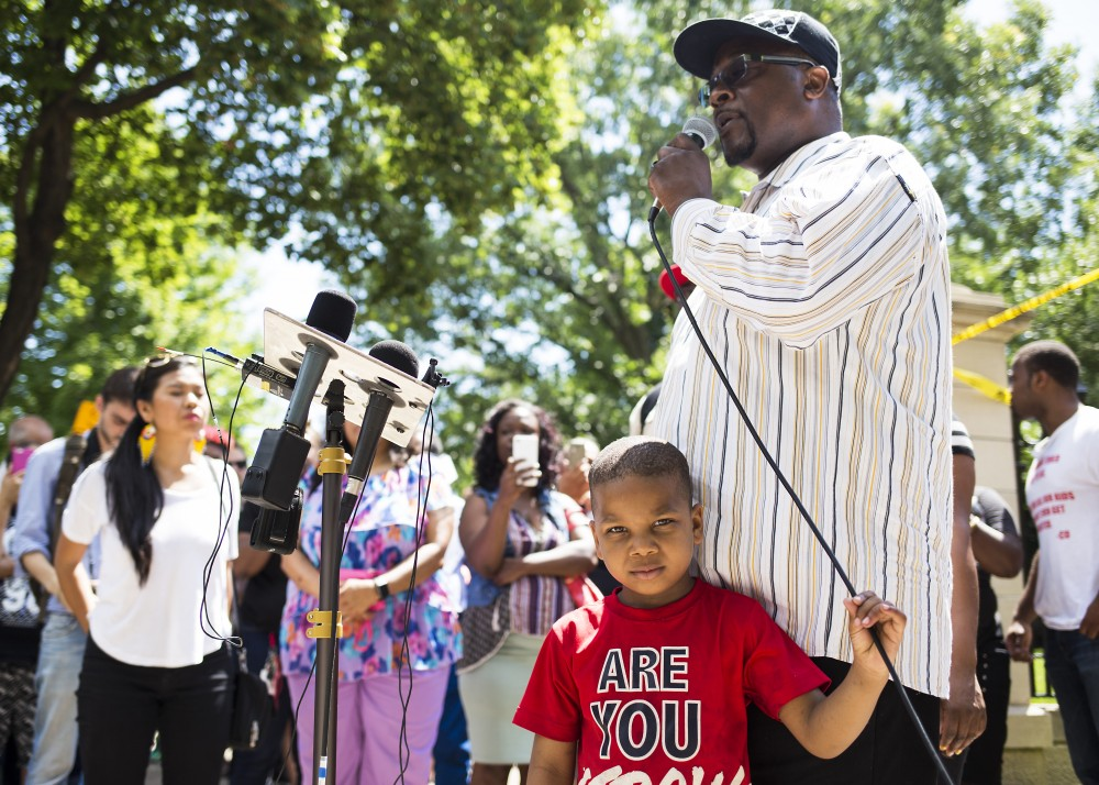 Pastor Thomas Mite, accompanied by his nephew Damarion, age 5, speaks to a crowd of community members outside of the Minnesota Governor's residence on Thursday, July 7.