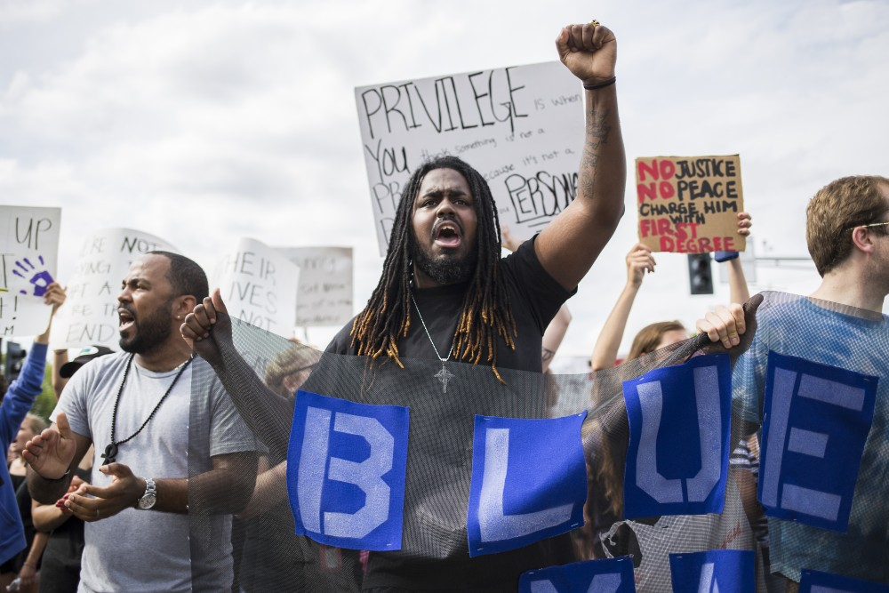 Aaron Allen of St. Paul chants alongside other protesters in a march following a rally outside of the St. Anthony Police Department, where demonstrators demanded justice for Philando Castile on Sunday.