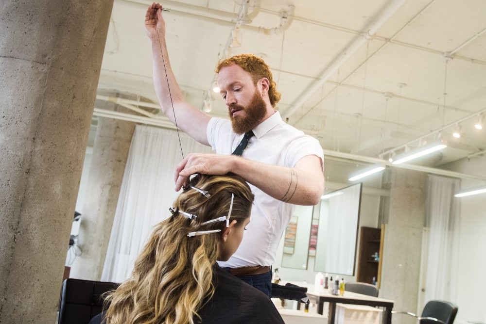 Hairstylist Adam Livermore demos the elastic thread hair style technique on Haus Manager Katie Dalager at the Haus Salon in the North Loop of Minneapolis on Sunday.