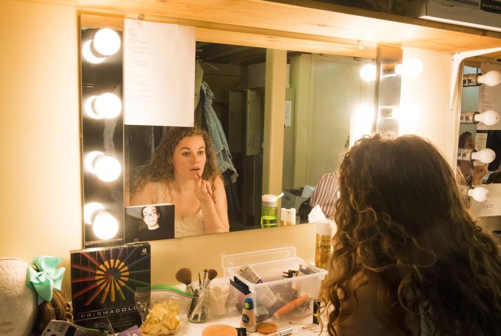 University student Kendall Kent applies makeup before the matinee show,