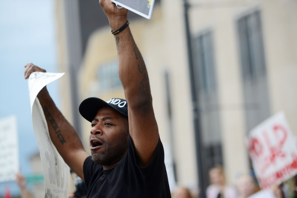 Demonstrator John Thompson chants with a crowd while marching down Kellogg Boulevard on Tuesday, Sept. 6, 2016 downtown St. Paul.