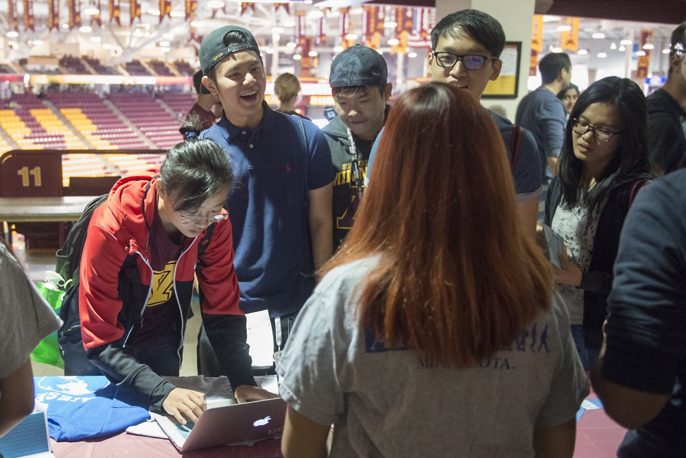 Psychology freshman Aurora Luo, far left, signs up to receive more information on student group AIESEC while other first year students speak with AIESEC representative Jenny Zhou at the Explore U activities fair held at Mariucci Arena on Saturday, Sept. 3, 2016. Luo is an international student from Beijing.