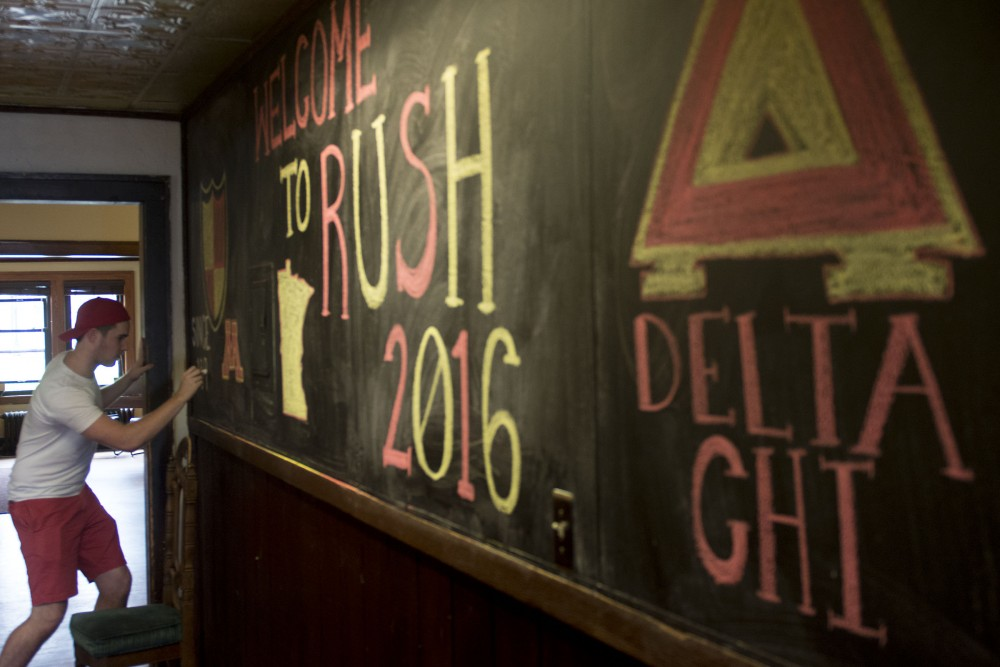 Biology and Spanish sophomore Will Richardson puts the finishing touches on Delta Chi's chalkboard mural on Sept. 5, 2016 at their fraternity house.