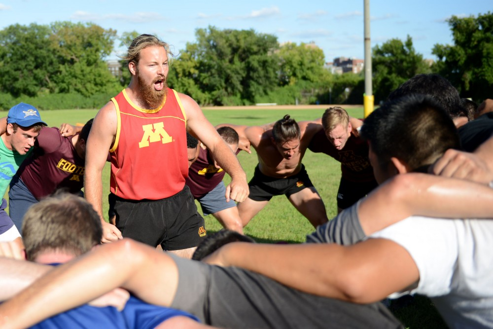 The University of Minnesota Club Rugby Team huddles as  David Sannerud chants in the center after their practice on Sept. 2, 2016. The team recently gained a new coach, Jimmy Hanson.