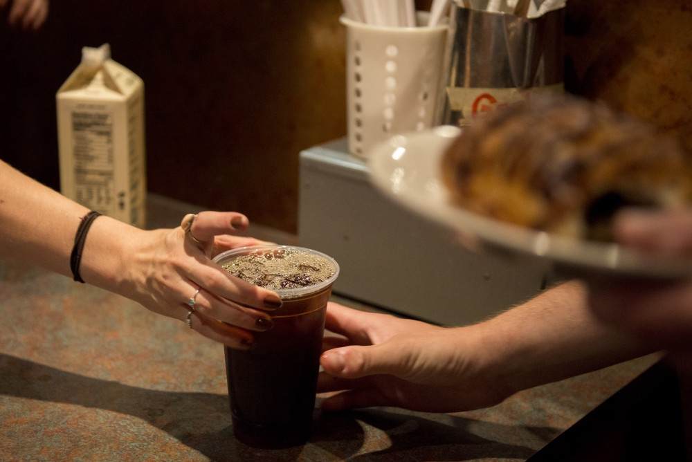 A barista hands a drink to a customer at Espresso Expos