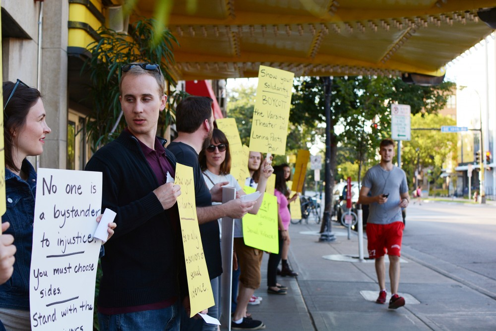 Demonstrators protest in front of the Varsity Theater bordering Fourth Street on Saturday, Sept. 10, 2016 in Dinkytown.