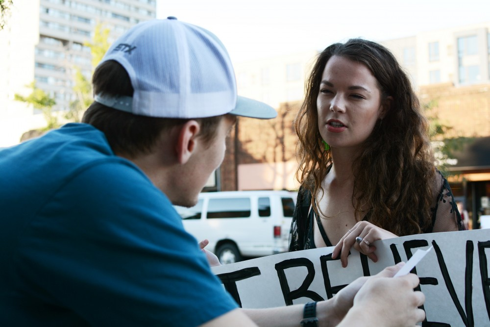 University alum and former Loring Pasta Bar employee Haley Purvis talks to passerby Alex Bogdanov as she protests against Jason McLean in front of the Loring Pasta Bar on Fourth Street on Saturday, Sept. 10, 2016 in Dinkytown. Purvis worked at Loring Pasta Bar for four months but quit because of the lawsuits.