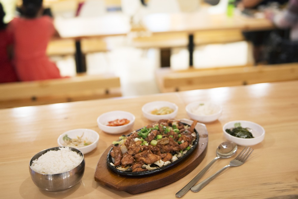 Kbop Korean Bistro serves up a Bulgogi entree with a choice of marinated chicken or beef on top a sizzling cast iron skillet in Dinkytown. The entrees include a variety of small sides that change frequently.