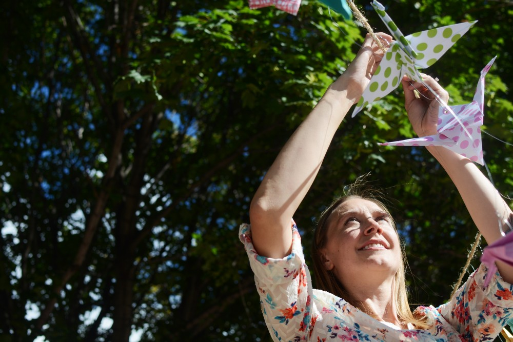 Landscape Architect Jennifer Krantz hangs up folded paper birds for the River of Birds installation on Saturday, Sept. 10, 2016 at Culture Park in St. Paul for the River Balcony Prototyping Festival. The Festival featured eleven art installations and live music that demonstrated ways for the public to better connect and interact with the river through the planned public pathway stretching along the St. Paul river bluff edge from the Science Museum to Union Depot.