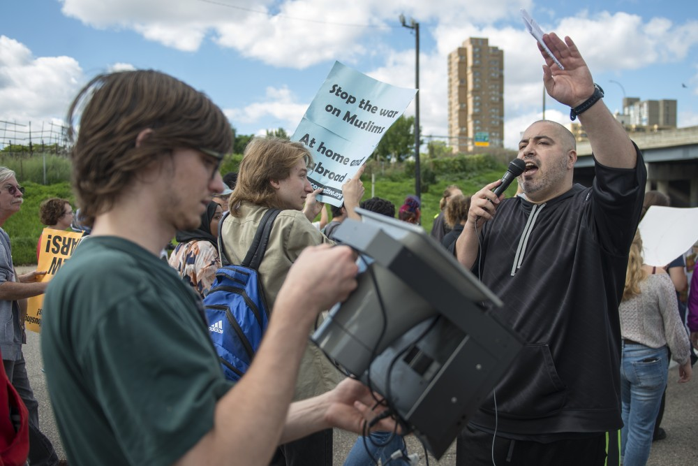 Sabers Wazwaz of the Anti-War Committee leads chants and speaks to the crowd of protestors from a portable megaphone during the march against islamophobia on Cedar Avenue on Saturday, Sept. 17, 2016.