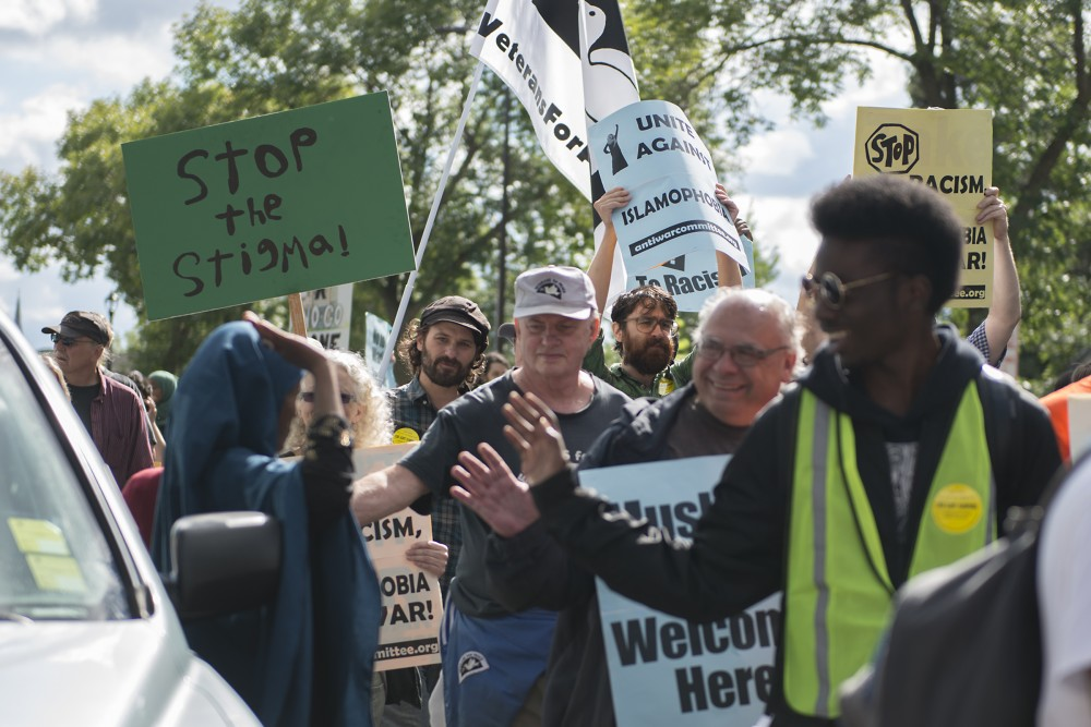 Protestors high-five a spectating woman and her children as they pass during the march against islamophobia on Cedar Avenue on Saturday, Sept. 17, 2016.