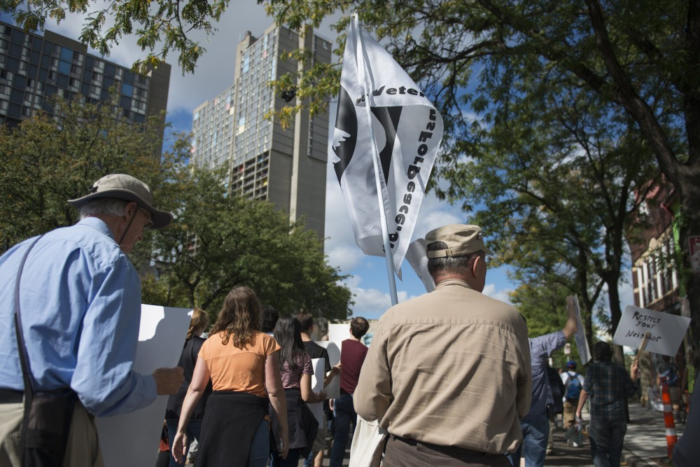 Ron Staff, Secretary of Vets For Peace chapter 27, carries a flag during the march against islamophobia through the Cedar-Riverside neighborhood on Saturday, Sept. 17, 2016.