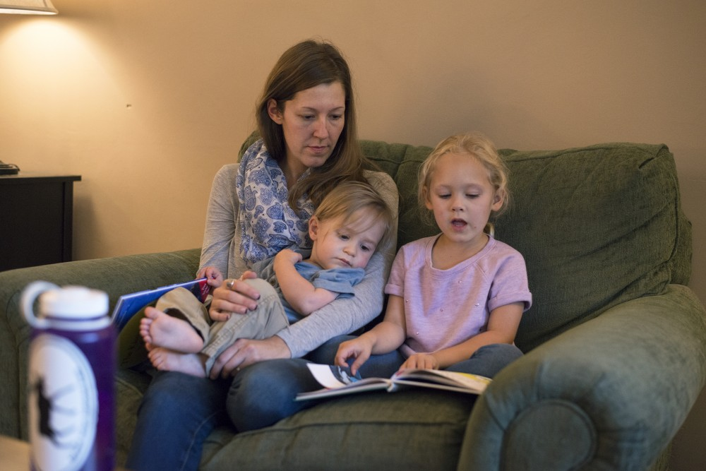 Annabelle Stalboerger reads to her two children, 18-month-old E.J., and 5-year-old Clara on Thursday, Sept. 15, 2016 at their home in Sartell, Minnesota. Stalboerger's fiancé University of Minnesota third-year law student Edward