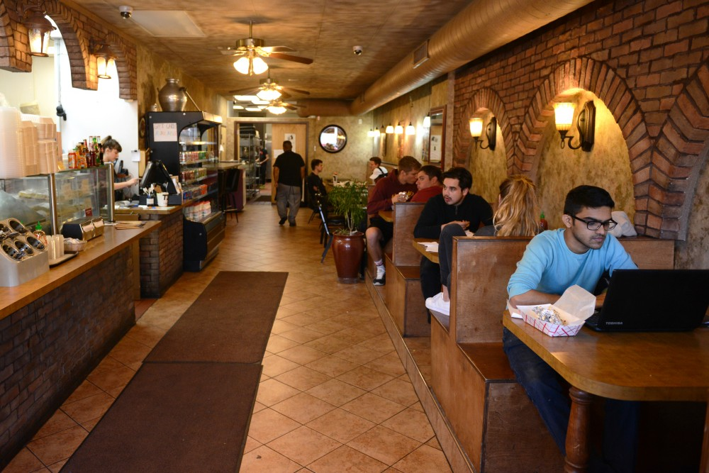 Patrons of Wallys Falafel and Hummus in Dinkytown chat and enjoy food on Sept. 26, 2016. The restaurant is an affordable staple in the area.