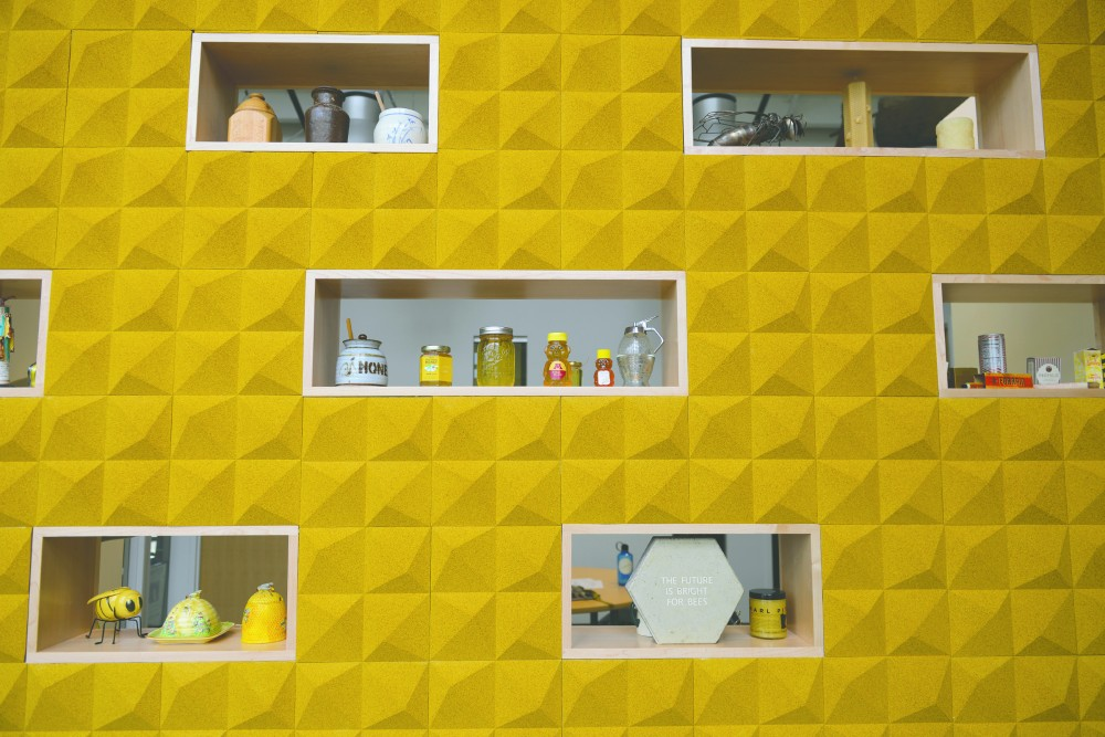 Bee-related collectibles sit on display on a honeycomb-inspired shelving unit at the new Bee Lab on Sept. 23, 2016.