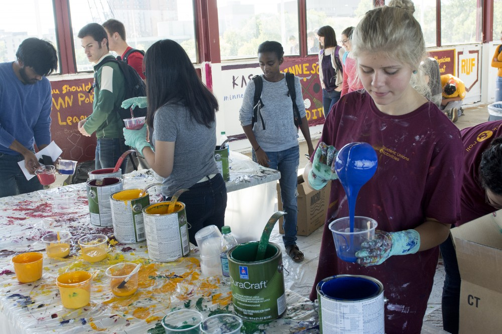 Piano performance freshman Bekah Klemp pours a cup of paint in the Washington Avenue Bridge on Friday, Sept. 30, 2016. Student Unions and Activities buys 130 cans of paint for the bridge painting every year.