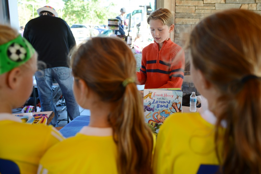 A group of girls look on as Frank Kamish displays his book Frank Henry and the Zooband Band at Elmcrest Park in Ramsey on Oct. 1, 2016. Frank, a fifth grader at Lake Harriet elementary, illustrated the book which he created alongside his father, Paul, and his uncle, David.