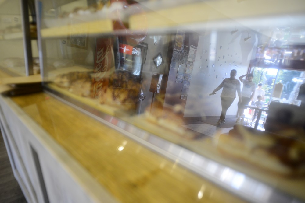 Customers, reflected in the doughnut case, walk into Sssdude-Nutz on Saturday, Oct. 1, 2016 in Dinkytown. Sssdude-Nutz has just celebrated its one year anniversary and Tim Horton's has signed a lease to move in next door.