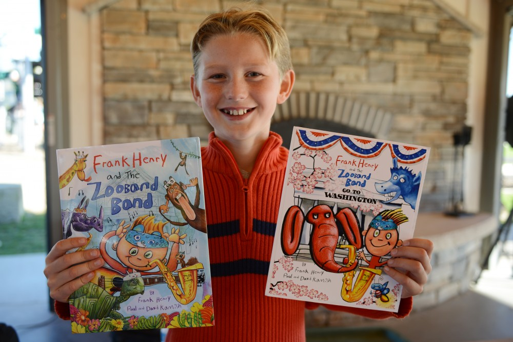 Frank Kamish holds up copies of his books at Elmcrest Park in Ramsey on Saturday. Kamish, who illustrated the books on display, is a fifth grader at Lake Harriet Elementary. Kamish creates books with his father, Paul, and his uncle, David.