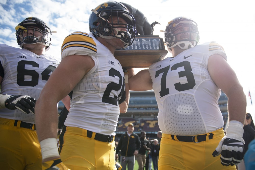 The Iowa Hawkeyes hoist up the Floyd of Rosedale rivalry trophy following their victory over the Gophers at TCF Bank Stadium on Oct. 8, 2016.
