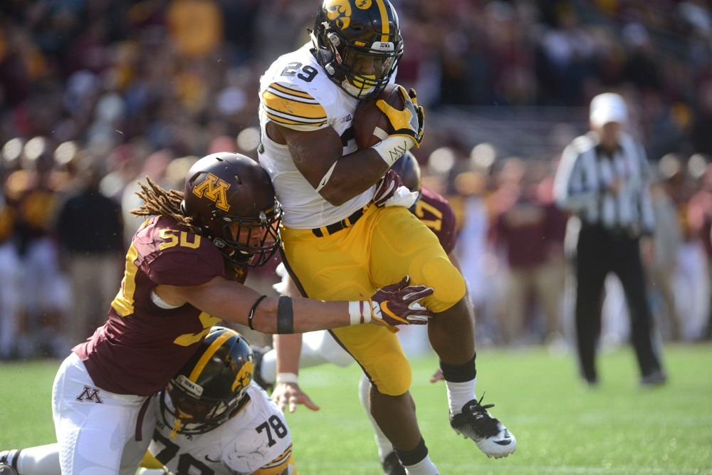 Hawkeyes running back Leshun Daniels, JR. is tackled by linebacker Jack Lynn on Oct. 8, 2016 at TCF Bank Stadium.