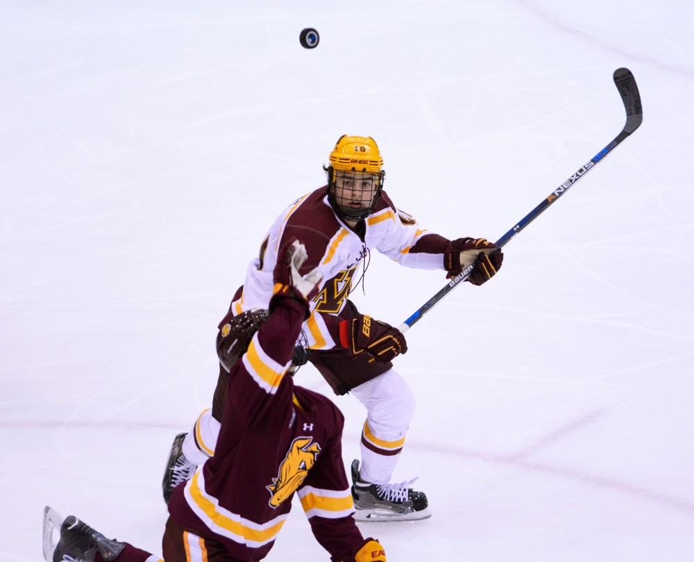 Gophers forward Brent Gates chases down a Duluth player attempting to catch the puck in the second period at Mariucci Arena on October 16, 2015.