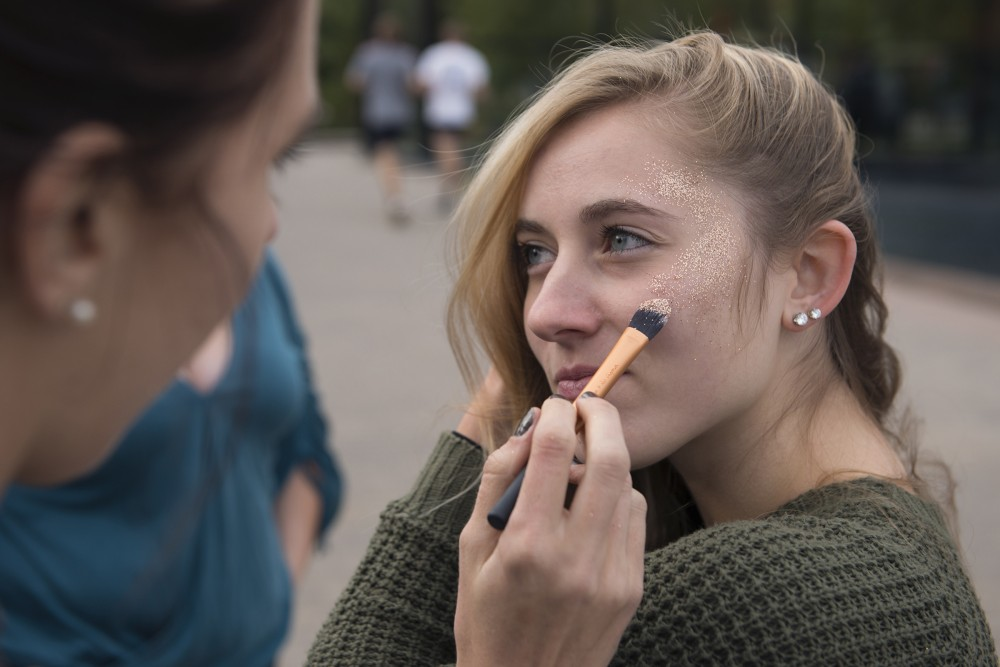 Undeclared freshman Lily Dunbar undergoes a glitter makeover before the Kesha concert outside McNamara Alumni Center on Friday.