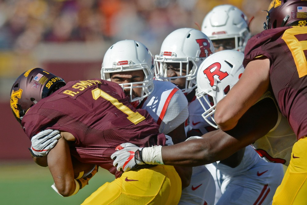 Running back Rodney Smith is tackled on Saturday at TCF Bank Stadium.