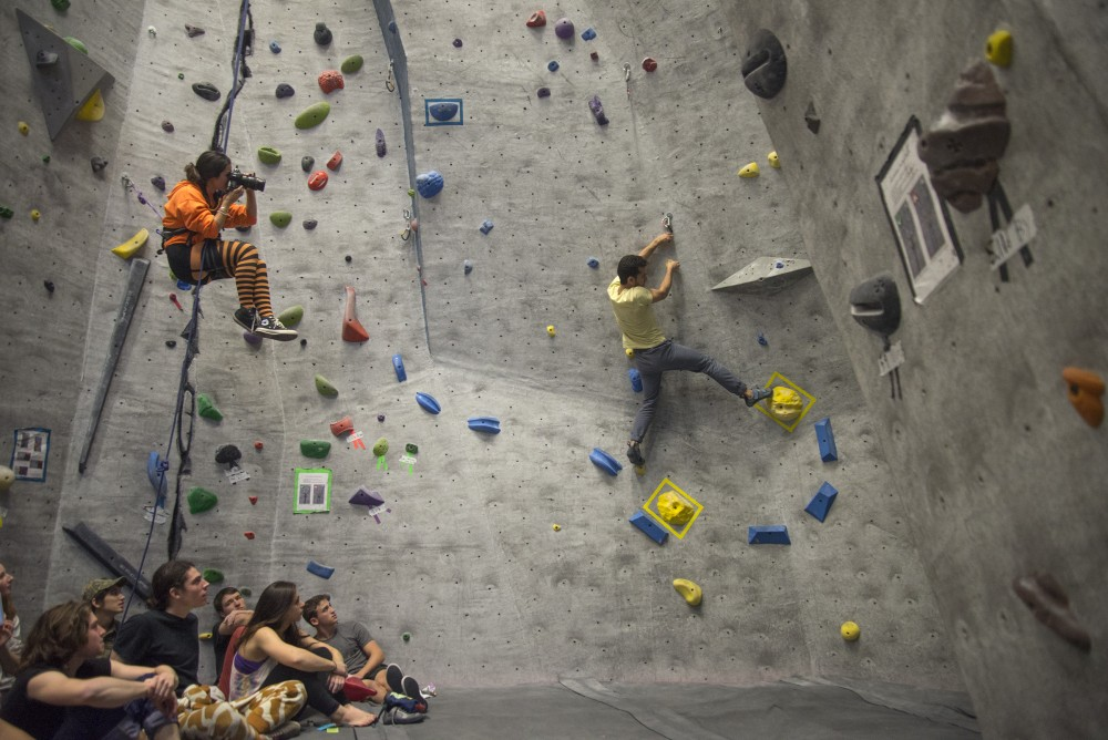 Hussuain Sajjad climbs the new boulder route on Saturday, Oct. 29, 2016 at the University Recreation and Wellness Center Climbing Gym. The Minnesota Climb Team hosted their second annual Crush O' Lantern competition there.