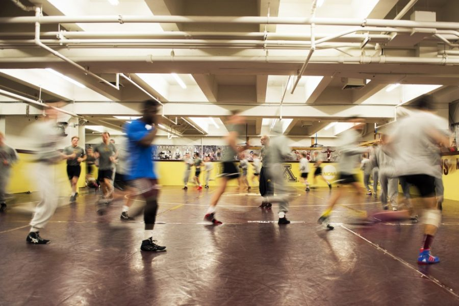 The wrestling team runs circles around their practice room for a cardio warm-up at the start of practice.