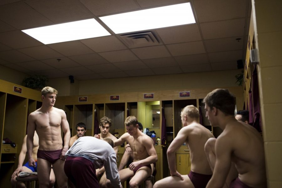 Stripped down to briefs, the wrestling team awaits individual inspection by a match official as well as weigh-ins inside their locker room in the Sports Pavilion.