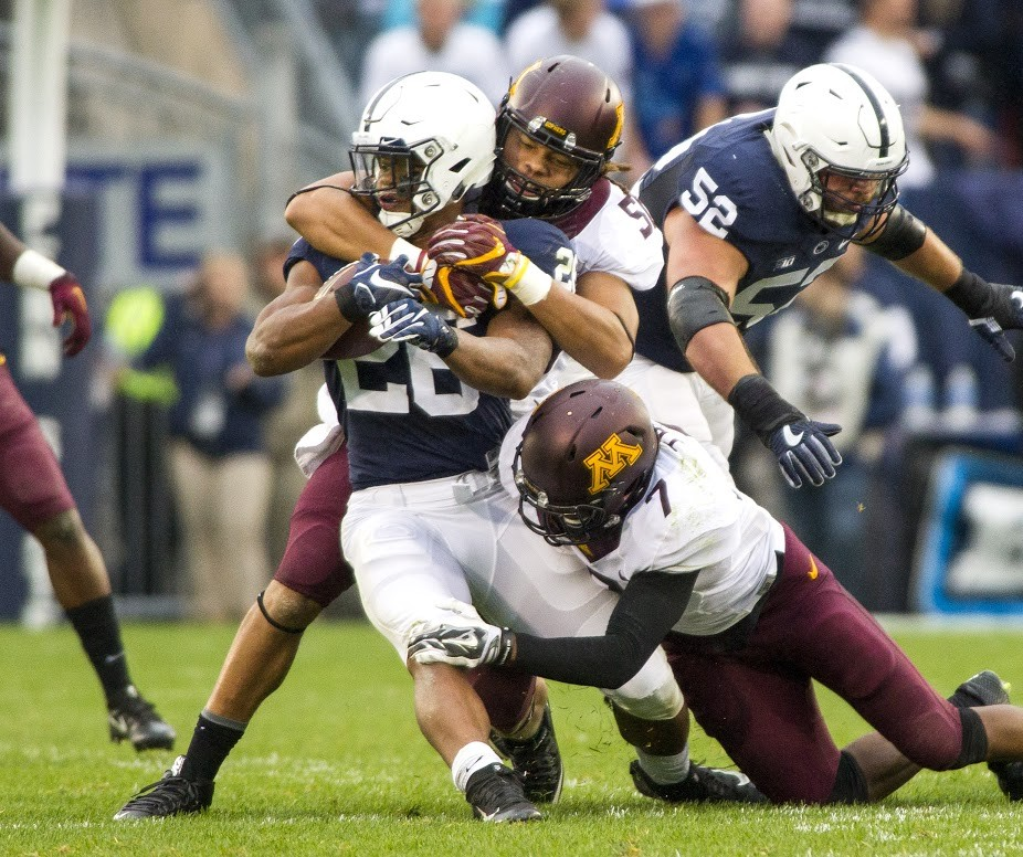 Penn State running back Saquon Barkley wrapped up by Minnesota linebacker Jack Lynn and defensive back Damarius Travis during the game at Beaver Stadium on Oct. 1, 2016.