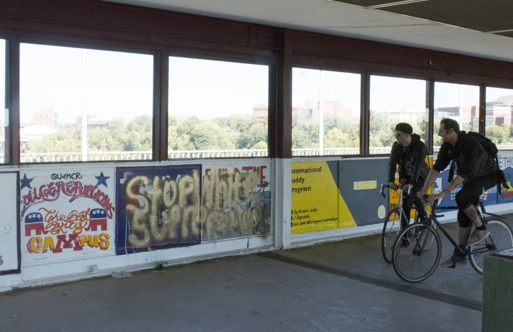 (left to right) Joseph Fagerhaugh and Aaron Rustand check out the vandalized panel in the Washington Avenue Bridge on Saturday, Oct. 1, 2016.
