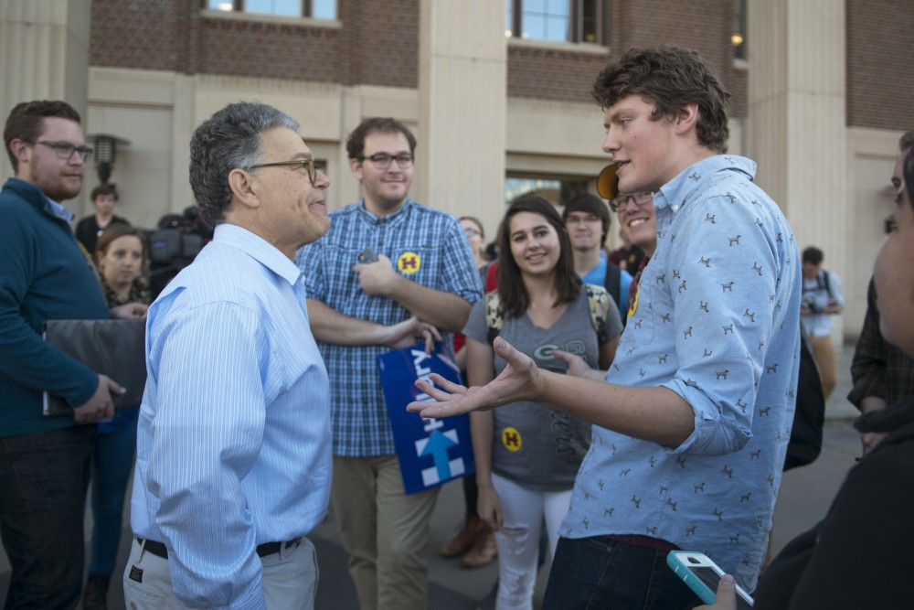 President of College Democrats at the University of Minnesota, Braxton Haake, right, talks to U.S. Sen. Al Franken on Friday, Nov. 4, 2016 outside of Coffman Union. Minnesota Democrats held a rally encouraging students to get involved and vote.