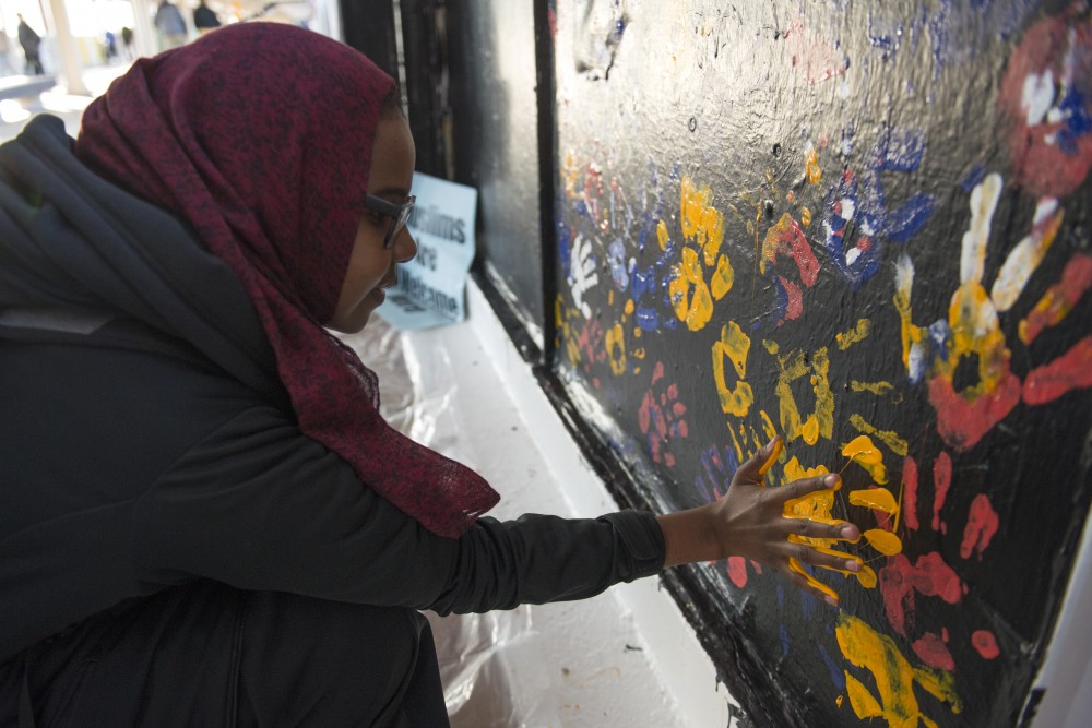 Psychology junior Fardowsa Hassan presses her painted hand on the Muslim Students Association's panel in the Washington Avenue Bridge inside the Washington Avenue Bridge on Friday.