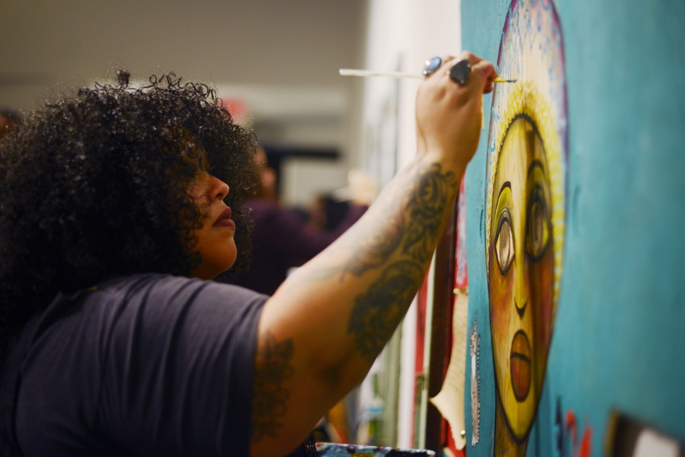 Artist Joy Spika works on a live painting at the launch party for the artist organization