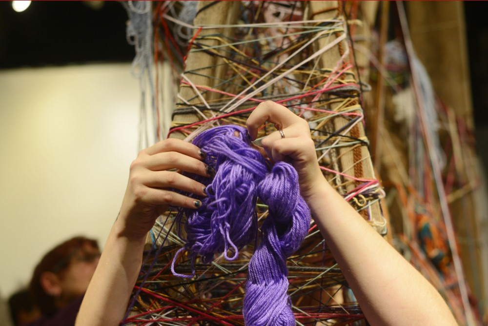 Artist Mary Allen wraps herself in string for a piece titled Link, Wrap, Tie, Build, Bind, and Free at the launch party for the artist organization A Conspiracy of Strange Girls at CO Exhibitions on Nov. 12, 2016 in Minneapolis.