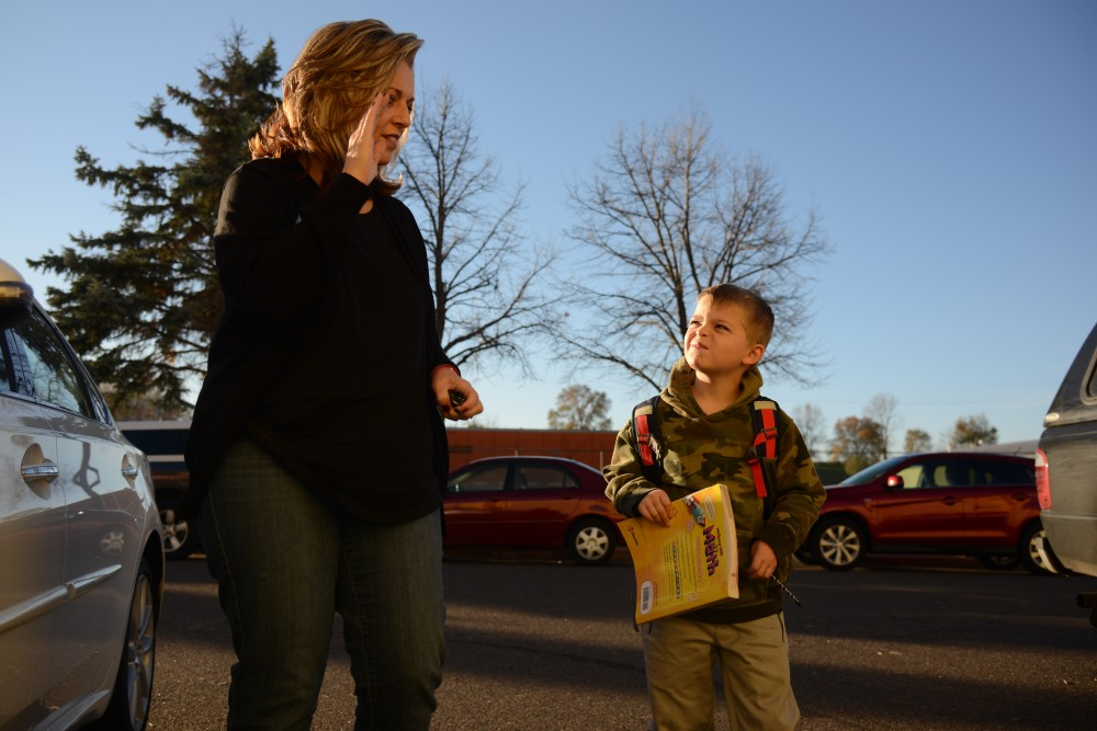 Amy Caslow signs to her son Asher Caslow, 6, while walking him into Metro Deaf School in St. Paul on Wednesday, Nov. 16, 2016.