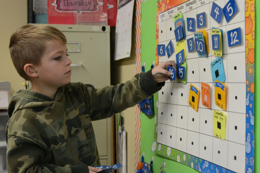 Asher Caslow, 6, adds a date to his class' calendar at Metro Deaf School in St. Paul on Wednesday, Nov. 16, 2016.