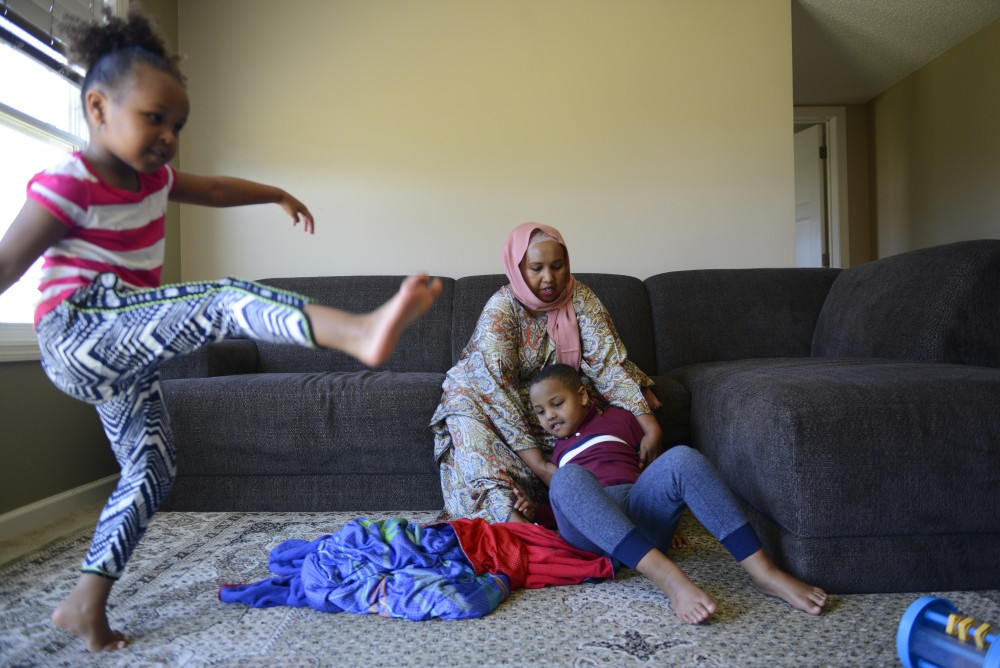 Marian Ahmed calms down her 6-year-old son, Anas, as 4-year-old Edna entertains herself, on Sunday, Nov. 6, 2016 at their home in Savage, Minnesota. Ahmed has four children, two boys and two girls. Both of her sons, Anas and Ayub have autism.