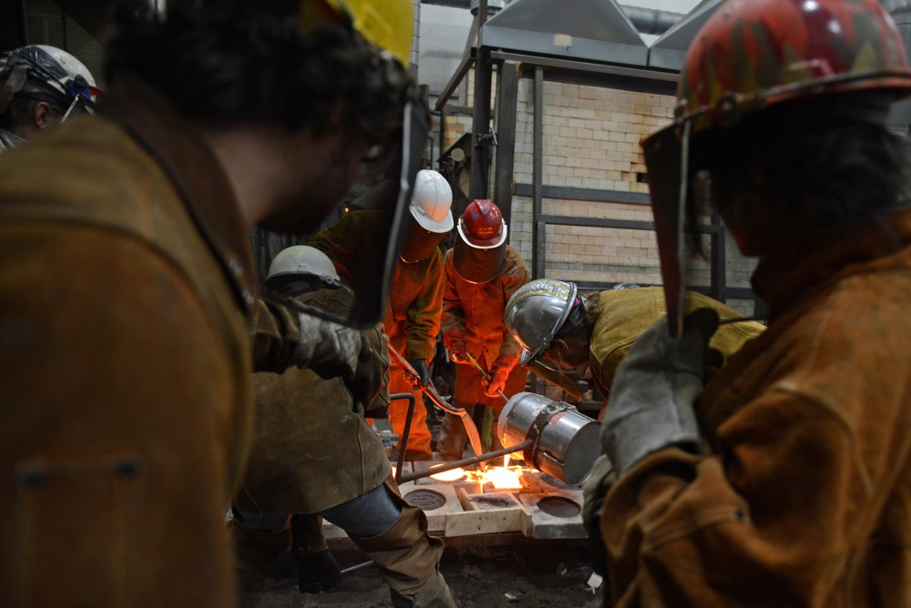 Participants in the 30th annual Iron Pour look on as a group works in the foundry at the Regis Center for Art on Nov. 18, 2016.