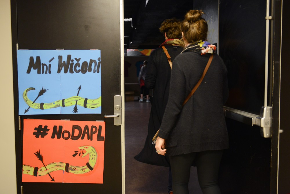 Attendees enter the Whole Music Club for the Stand With Standing Rock benefit event on Nov. 28, 2016. The event was hosted to raise money and awareness for the Dakota Access Pipeline occupation happening in North Dakota.