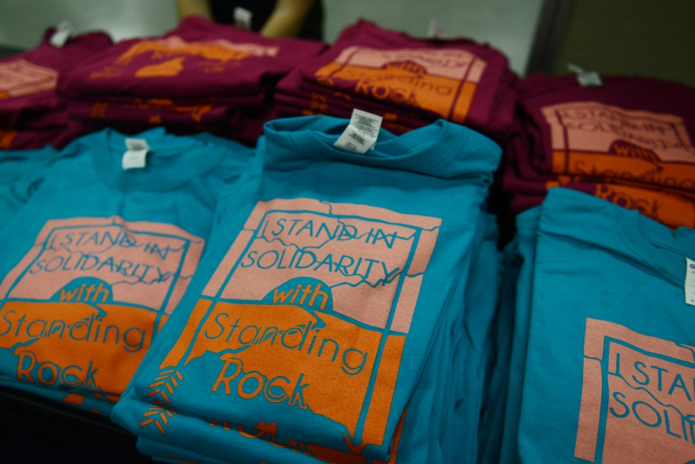 T-shirts for sale reading I stand in solidarity with Standing Rock sit on a table at the Stand With Standing Rock benefit event at the Whole Music Club on Nov. 28, 2016.