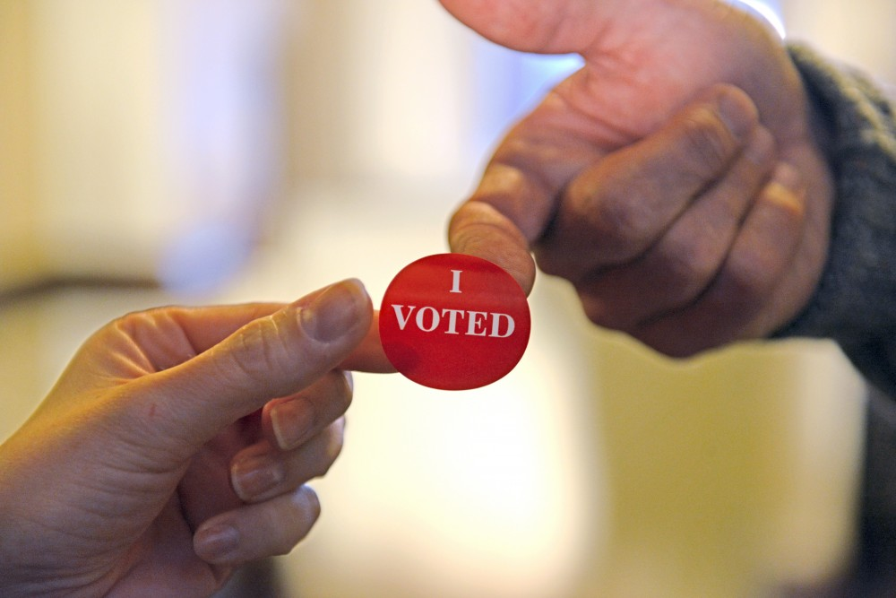 A voter is handed an I Voted sticker after casting her vote at First Congressional Church in the Marcy Holmes neighborhood on Nov. 8, 2016. Polls opened at 7 a.m. and hundreds of voters came out early to cast their votes.