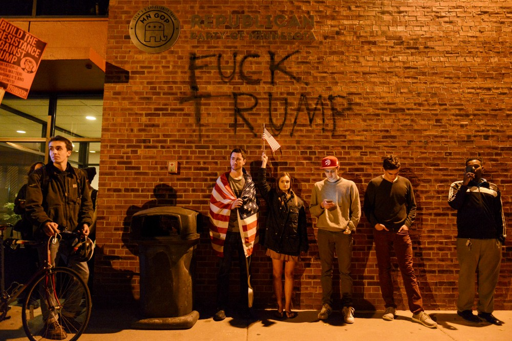 Sophomores Sam Peterman, Lydia Fess, Andrew Carlson and Tait Anderson stand outside the Republican Party of Minnesota headquarters at a protest against Donald Trump on Nov. 10, 2016.