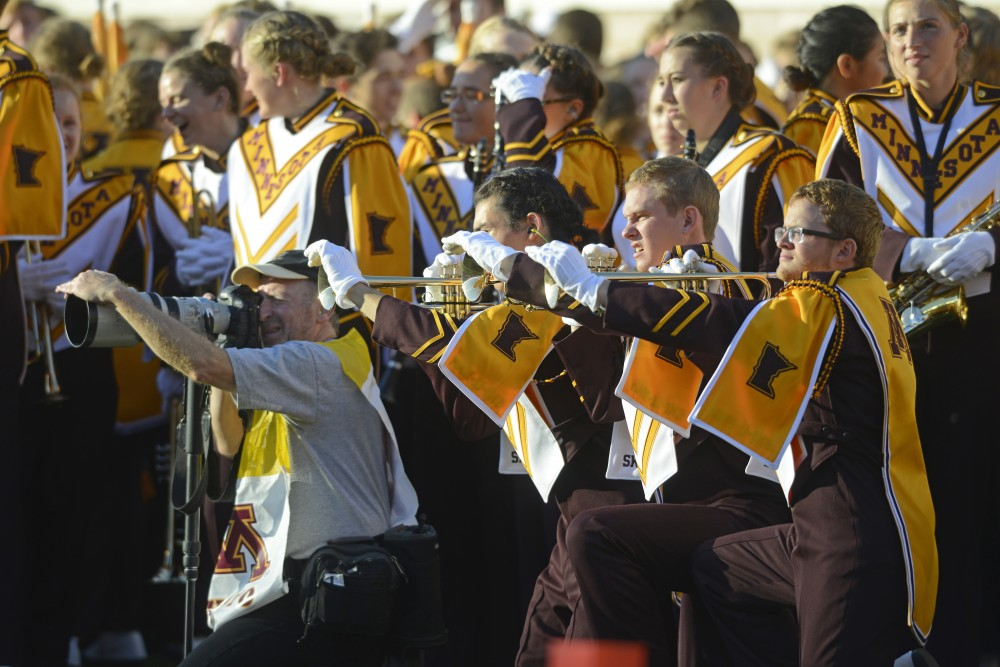 Members of the University of Minnesota Marching Band imitate a photographer before halftime at TCF Bank Stadium on Nov. 5, 2016.