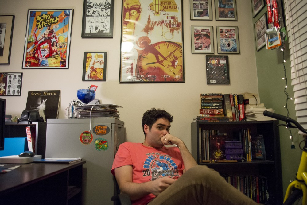 Comic book writer Eliot Rahal poses in his office in front of his published comic books at his home in Minneapolis on Monday, Nov. 28, 2016.